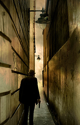 Man Staning in Alleyway with Gun - p1072m993474 by miguel sobreira