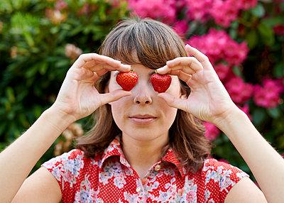 Frau hält sich Erdbeeren vor die Augen - p1124m1134766 von Willing-Holtz