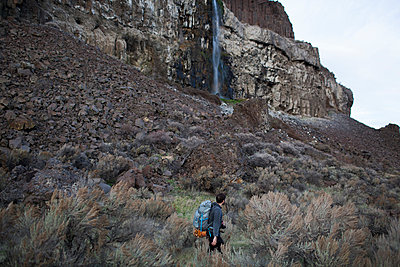 Side view of hiker with backpack walking on field against mountain - p1166m1486227 by Cavan Images