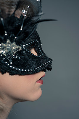 Side portrait of glamorous blonde Woman wearing a black velvet and lace face mask. - p1433m1584195 by Wolf Kettler