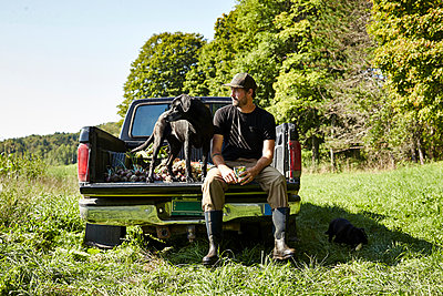 A farmer and his dog sit in his truck after harvesting vegetables. - p343m1203843 by Josh Campbell