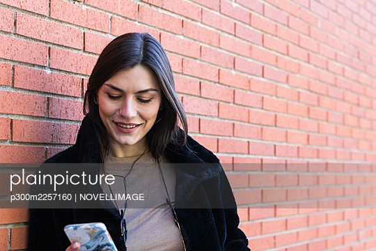 Smiling woman with mobile phone listening music through headphones while leaning brick wall - p300m2257160 by NOVELLIMAGE