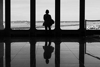 Frau guckt auf die Landebahn in einer Wartehalle - p1085m2007820 von David Carreno Hansen