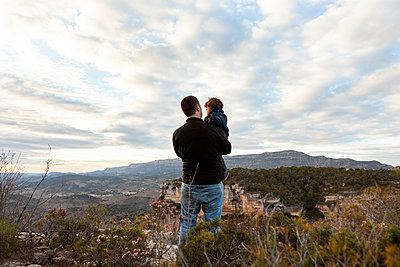 Back view of father carrying little son in Siurana mountains - p1166m2190755 by Cavan Images