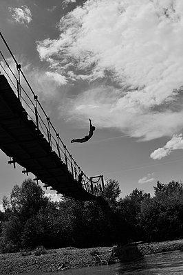 Boy jumping from the bridge into the river - p1412m1467284 by Svetlana Shemeleva