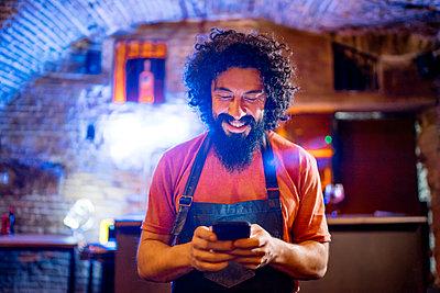 Young man, working in bar, using smartphone - p300m2159911 von Jesús Martinez