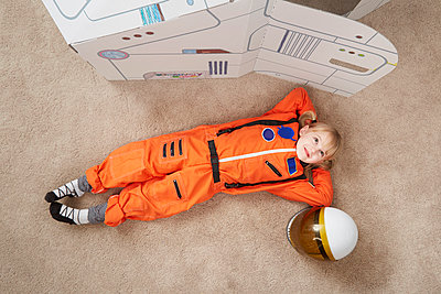 Young girl playing, wearing astronaut outfit, lying next to cardboard spaceship, elevated view - p924m1030225f by Stanton j Stephens