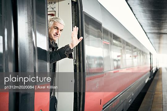 Mann winken Bahnhof Zug - p1312m2020084 von Axel Killian