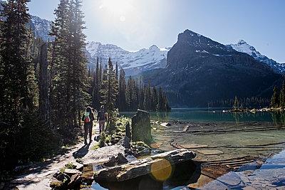 Women hiking along tranquil, idyllic mountain lake - p1023m2066505 by Jarusha Brown
