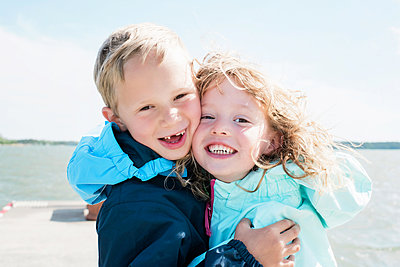 portrait of brother and sister laughing and hugging at the beach - p1166m2201764 by Cavan Images