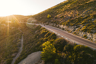 Italy, Elba Island, biker on coastal road against the sun, aerial view with drone - p300m2070069 by Francesco Buttitta