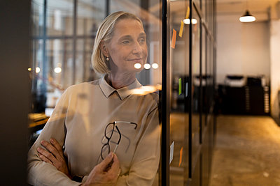 Mature businesswoman looking at adhesive notes on glass pane in office - p300m2154935 by Gustafsson