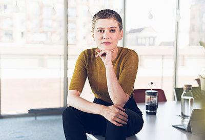 Portrait of businesswoman sitting on desk in office - p300m2214176 by Uwe Umstätter