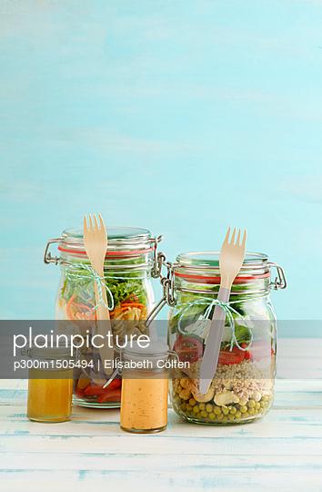 Preserving jars of various mixed salad and jars of salad dressings - p300m1505494 by Elisabeth Cölfen