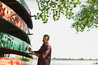 A man stacking narrow rowing boats and lashing them onto a trailer or stand.  - p1100m876301f by Jamie Kripke