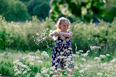 Portrait of smiling little girl playing with seeds of blowball - p300m2114823 von Oxana Guryanova
