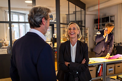 Smiling businesswoman and businessman talking in office - p300m2156011 by Gustafsson
