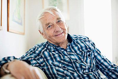Portrait of smiling elderly man sitting in living room - p4269316f by Maskot