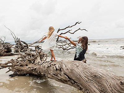 Caucasian mother and daughter walking on driftwood on beach - p555m1504321 by Marc Romanelli