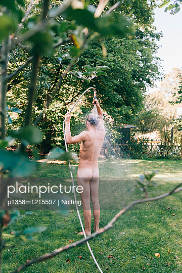 Junger Mann duscht mit Gartenschlauch - p1358m1215597 von Nolting