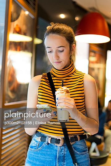 Spain, teenage girl with milk shake using smartphone - p300m2103158 by Eloisa Ramos