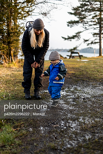Full length of mother looking at son standing on dirt in park - p426m2296222 by Maskot