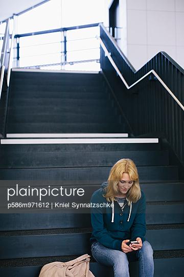 Blonde Studentin mit Smartphone im Treppenhaus - p586m971612 von Kniel Synnatzschke