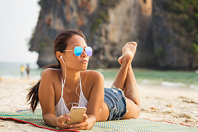Woman listening music through smart phone while lying on mat at beach - p1166m1163971 by Cavan Images