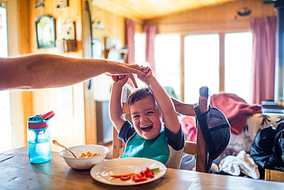 Father reach to tickle his son while at the table - p1166m2147324 by Cavan Images