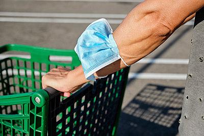 Man pushing a shopping cart wearing his face mask in his hand - p1423m2210147 by JUAN MOYANO