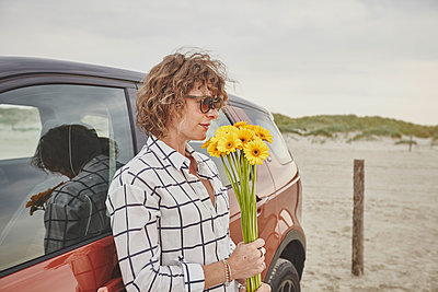 Woman with flowers leaning on car - p1573m2178913 by Christian Bendel