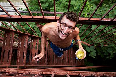 Caucasian man standing on urban fire escape drinking orange juice - p555m1303235 by Granger Wootz