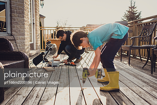 Father and son working on fixing a deck with power tools together. - p1166m2200196 by Cavan Images