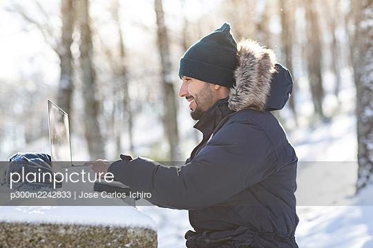 Smiling businessman working on laptop in snow sunlight - p300m2242833 by Jose Carlos Ichiro