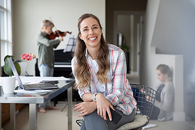 Portrait confident, happy mother working from home while children do homework and practice violin in background - p1192m2088267 by Hero Images