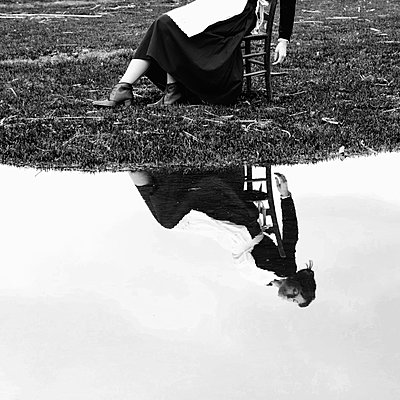 Reflection, Maid sitting on a chair next to lake - p1521m2158318 by Charlotte Zobel
