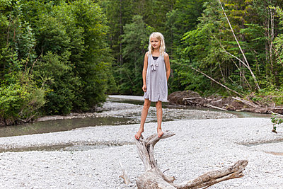 Girl standing on dead wood at the riverside - p300m2030365 von Tom Chance