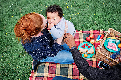 Parents playing with son while sitting on picnic blanket at park - p300m2287200 by Angel Santana Garcia