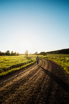 Farmer walking down rural road - p352m2119870 by Lena Katarina Johansson