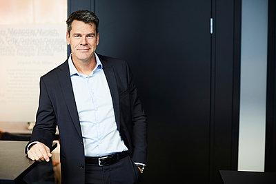 Portrait of confident mature businessman standing in office - p426m2074599 by Maskot