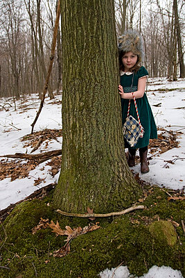Little girl hiding behind a tree - p5830090 by Kristina Williamson
