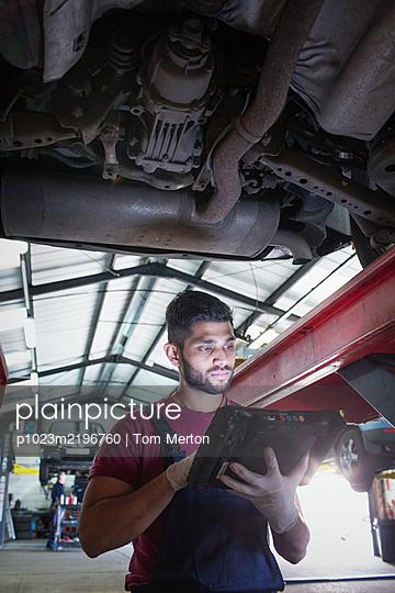 Male mechanic using diagnostic equipment under car in auto repair shop - p1023m2196760 by Tom Merton
