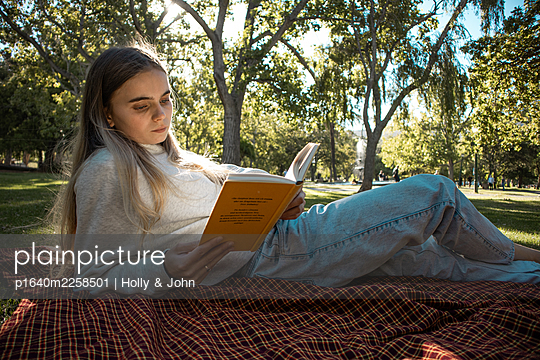 Teenage girl reading a book in the park - p1640m2258501 by Holly & John