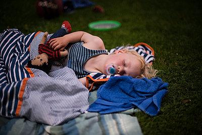 Kleiner Junge schläft auf einer Decke - p1046m1220949 von Moritz Küstner