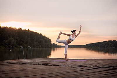 Woman practicing dance pose on pier by lake against cloudy sky during sunset - p1166m2011221 by Cavan Images