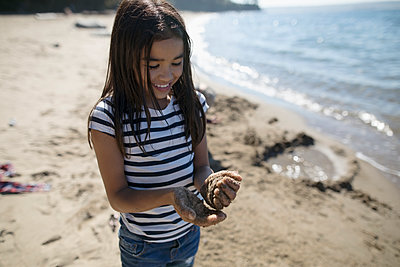 Girl playing with sand on sunny ocean beach - p1192m1511852 by Hero Images