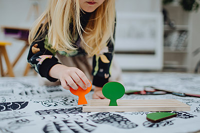 Blonde girl playing with wooden toys - p1414m2044909 by Dasha Pears