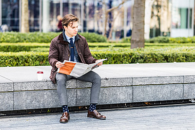 Businessman reading newspaper outdoors - p300m1580737 by William Perugini