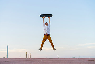 Young man jumping in the air holding a skateboard - p300m2028711 by VITTA GALLERY