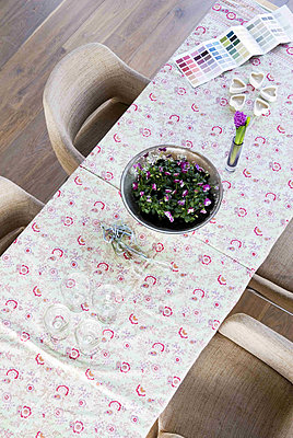 Overhead view of dining table with floral tablecloth and flower display - p349m790644 by Polly Eltes